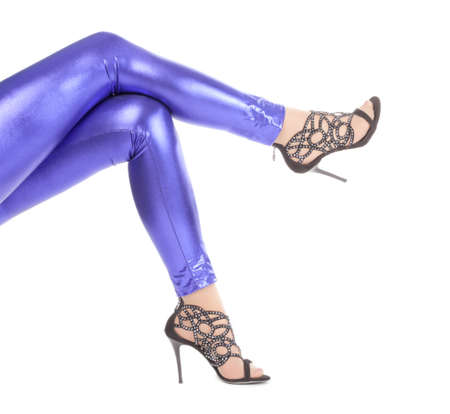 Cropped view image of a womans sexy legs clad in shimmering blue leggins and stilettos photo