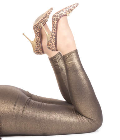 high heeled: Shapely sexy female legs in shiny golden leggins and stylish high heeled shoes Stock Photo