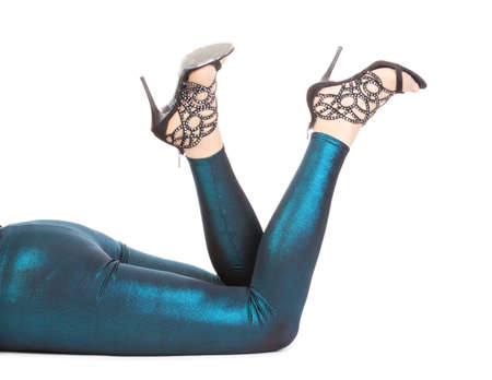 tantalising: Cropped view of a woman lying on the floor kicking her sexy shapely legs in shimmering tights and stilettos high in the air