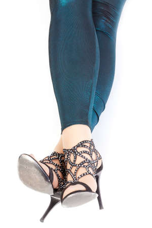 Shapely sexy female legs in shiny green leggins and stylish high heeled shoes Stock Photo