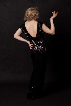 blondy: Full length portrait of drag queen, view from the back. Man dressed as Woman, on black background