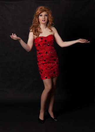 transexual: Retrato de cuerpo entero de drag queen. Hombre vestido como mujer, sobre fondo negro