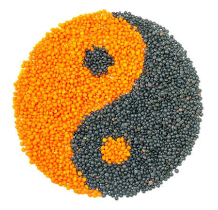 Orange and Black Lentil forming a yin yang symbol, isolated on white photo