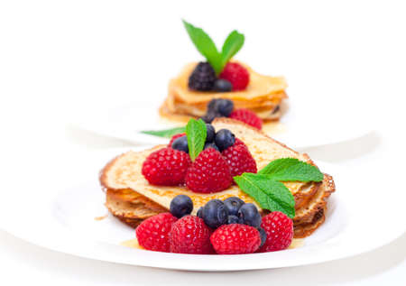 Delicious Freshly Prepared Pancakes with Honey and Berries on white background photo