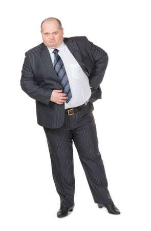 Fat túlsúlyos üzletember egy elegáns öltöny állt a kezét csípőre meredt a kamera egy elégedetlen kifejezést, stúdió portré fehér Stock fotó