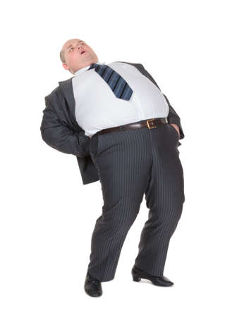 Very overweight man in a stylish suit and tie with acute back ache bending over backwards to alleviate the pain with an agonised expression on his face isolated on white photo