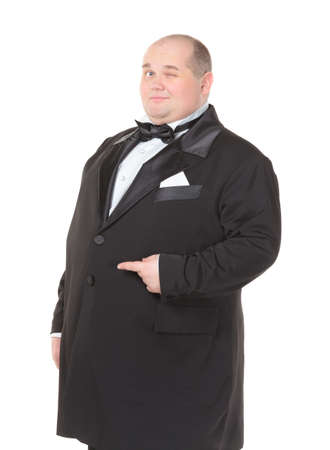 Elegant very fat man in a dinner jacket and bow tie winking mischievously and pointing with his finger across his belly , three quarter studio portrait on white