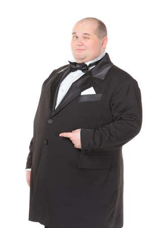 tuxedo man: Elegante uomo molto grasso in smoking e farfallino ammiccando maliziosamente e indicando con il dito sulla sua pancia, tre quarti ritratto di studio su bianco