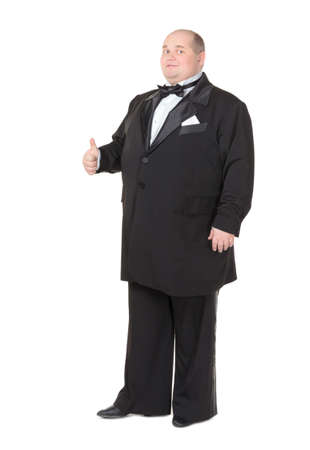Elegant very fat man in a tuxedo and bow tie shows thumb-up, on white background photo