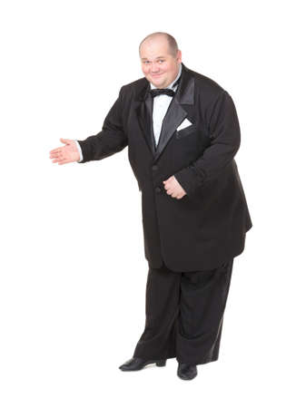 dinner jacket: Elegant fat man in a dinner jacket and bow tie smiling charmingly as he holds out his hand to the side gesturing in that direction