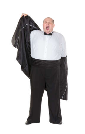 Very overweight elegant fat man yawning after a night out as he strips off his dinner jacket, studio portrait on white photo