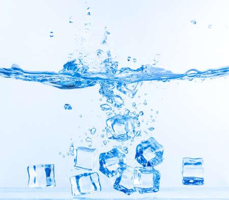 Ice Cubes gedaald in water met splash op wit Stockfoto