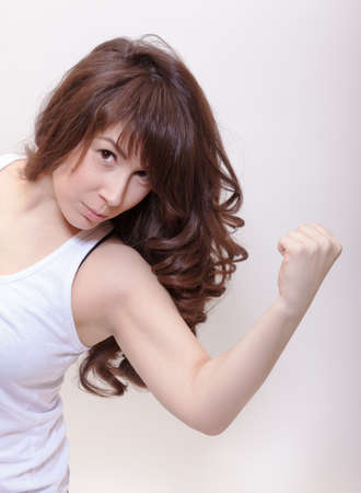 Attractive woman with long wavy brunette hair leaning forwards flexing her arm and making a fist as she looks at the camera photo