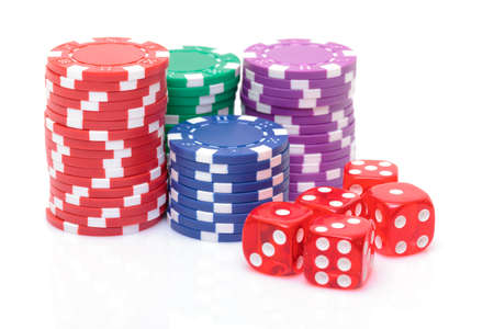 Stacks of Poker Chips with Playing Bones, closeup on white background photo