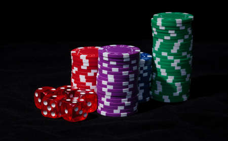 Stacks of Poker Chips with Playing Bones, closeup on black background photo