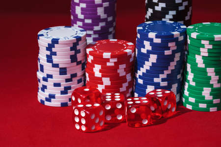 Stacks of Poker Chips with Playing Bones, closeup on red background photo