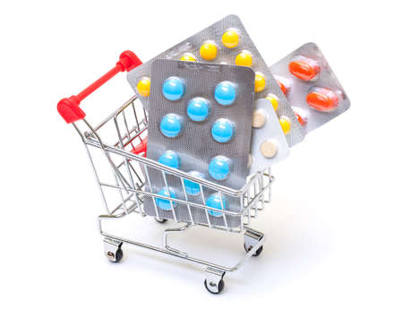 Multicolored pills packs in shopping cart, on white background photo