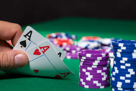 card game: Colorful poker chips and two Ace closeup on green cloth Stock Photo