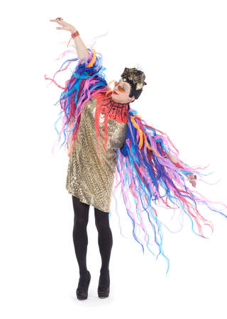 glitzy: Fashion conscious drag queen in a glitzy gold dress, high heeled stilettos and with streamers performing in a show, isolated on white