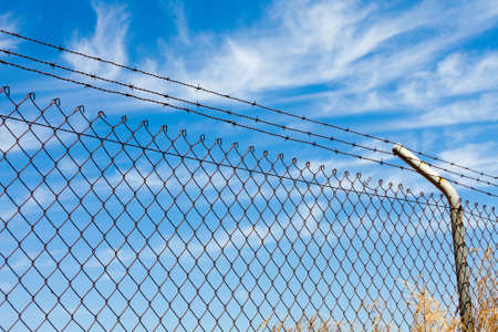 Mesh fence with barbed wire on a background of blue sky photo