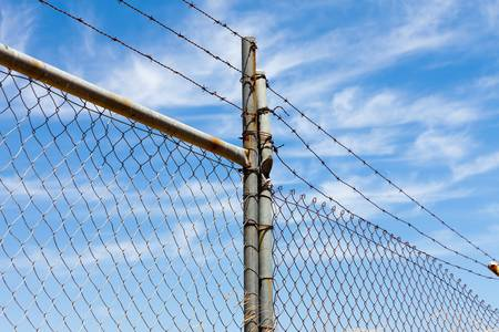 Mesh fence with barbed wire on a background of blue sky Stock Photo - 21759155