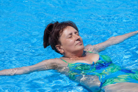 Middle-aged woman swims in the swimming pool, closeup photo
