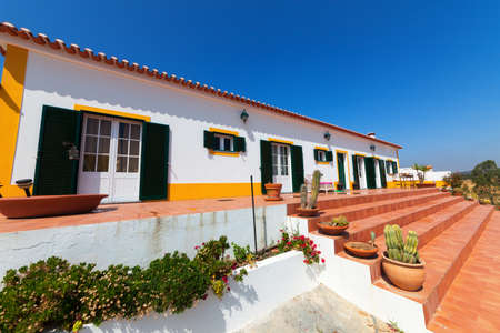 verandah: Modern accommodation with apartments or rooms leading off a common long exterior brick verandah with colourful yellow ornamentation and green shutters Stock Photo