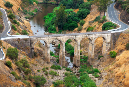 stone arches: Arched road bridge with high stone arches crossing a river bed in mountainous countryside with tarred roads