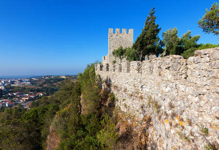 valley below: Perimeter fortified stone wall with a lookout tower and crenellations of a castle or fortified walled medieval town with a view out over the valley below