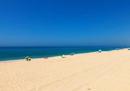bathers: Bella spiaggia tropicale con bagnanti relax su una distesa di sabbia dorata accanto a un oceano blu calmo sotto il sole estivo Archivio Fotografico