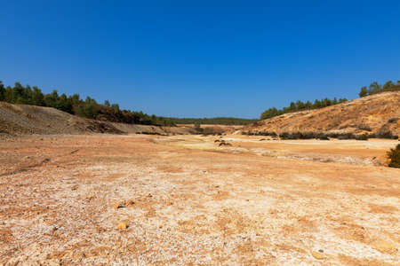 riverbed: Empty river-bed in a dry dusty landscape with distant trees on the horizon Stock Photo