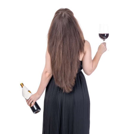 Woman with a bottle of red wine and a wineglass standing with her back, on white photo