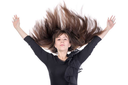 Young woman with her long straight brunette hair flying in the air and her arms raised above her head isolated on white photo