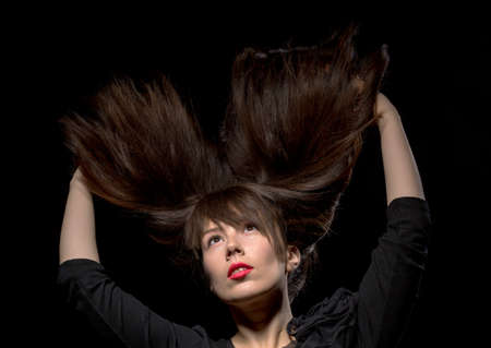 Young woman with her long straight brunette hair flying in the air and her arms raised above her head isolated on black photo