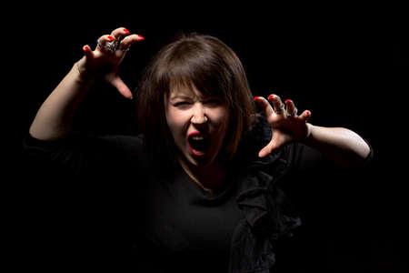 clawing: Donna che getta un capriccio urla di rabbia e graffiando l'aria con le sue mani su uno sfondo scuro