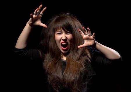 clawing: Donna, lanciando un capriccio urlando di rabbia e graffiando l'aria con le sue mani su uno sfondo scuro