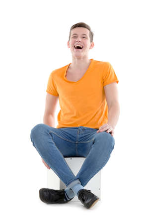 hilarity: Funny young man, wearing a yellow T-shirt and slim jeans, laughing out loud while sitting on a cube, isolated