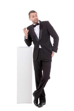 quizzical: Hombre delgado elegante con un traje y corbata de lazo inclinado indiferentemente en un pedestal blanco con una expresi�n burlona carism�tico