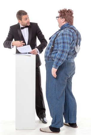 Elegant man in a tuxedo and bow tie standing arguing with an overweight country yokel