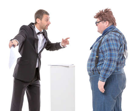 unyielding: Elegant man in a suit and bow tie standing arguing with an overweight country yokel in braces trying to persuade him to move in a certain direction to no avail Stock Photo