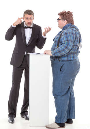 unyielding: Elegant man in a tuxedo and bow tie standing arguing with an overweight country yokel