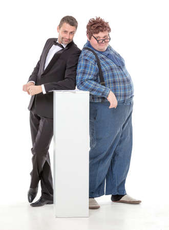 unyielding: Elegant man in a tuxedo and bow tie standing with an overweight country yokel Stock Photo