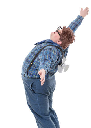 pretense: Overweight obese young man standing with his back arched and arms outstretched and a small propeller blade on his back  Stock Photo