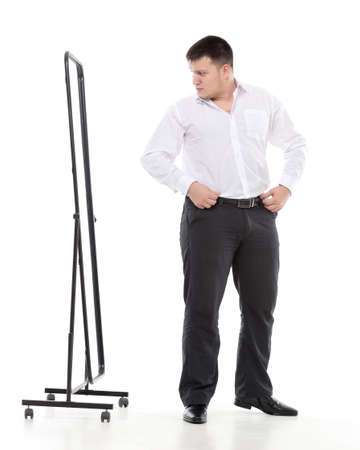 Overweight man admiring himself in a standing mirror as he checks the fit of his clothing and his appearance while dressing in the morning photo