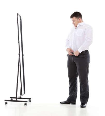 Túlsúlyos férfi megcsodálta magát a tükörben állva, miközben ellenőrzi a fit ruháját, és ő megjelenése, míg öltözködés reggel Stock fotó