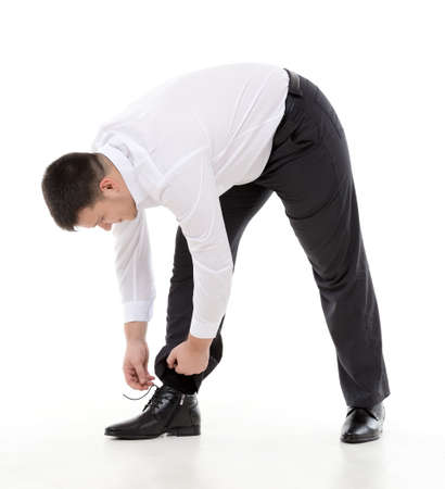 supple: Supple businessman bending down to do up his shoelaces on his stylish leather shoes while dressing in the morning or because they have come loose during the day