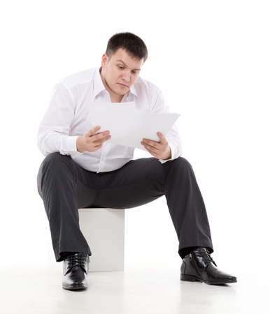 disbelief: Businessman reading a report with scepticism raising his eyebrow in disbelief at the information