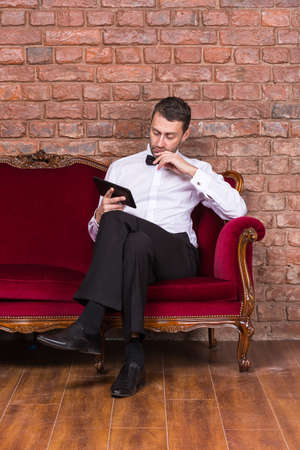 nonchalant: Conceptual image of an elegant businessman lying relaxing on a settee against a brick wall and reading tablet