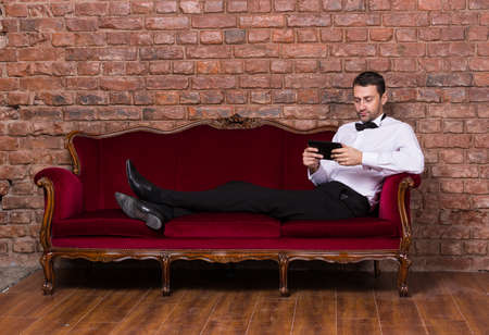 Conceptual image of an elegant businessman lying relaxing on a settee against a brick wall and reading tablet