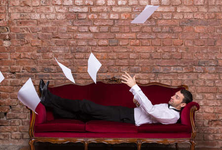 settee: Conceptual image of an elegant businessman lying relaxing on a settee against a brick wall with flying paperwork floating in the air above him